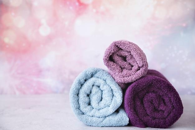 Vista frontal de toallas apiladas con colores de fondo Foto Premium