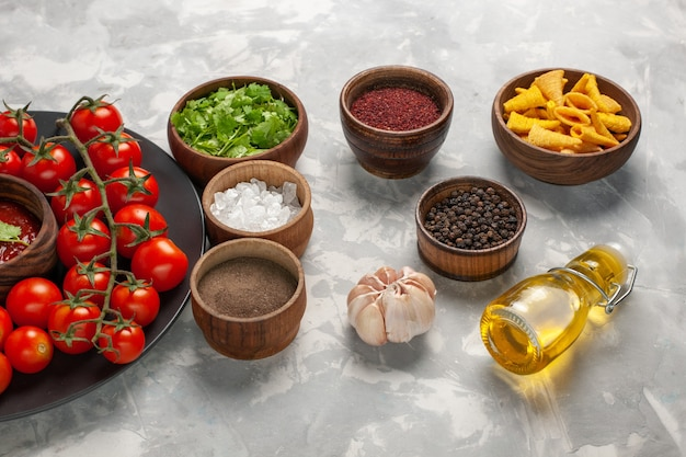 Vista frontal de los tomates cherry frescos dentro de la placa con diferentes condimentos en la superficie blanca comida vegetal ensalada de salud alimentaria
