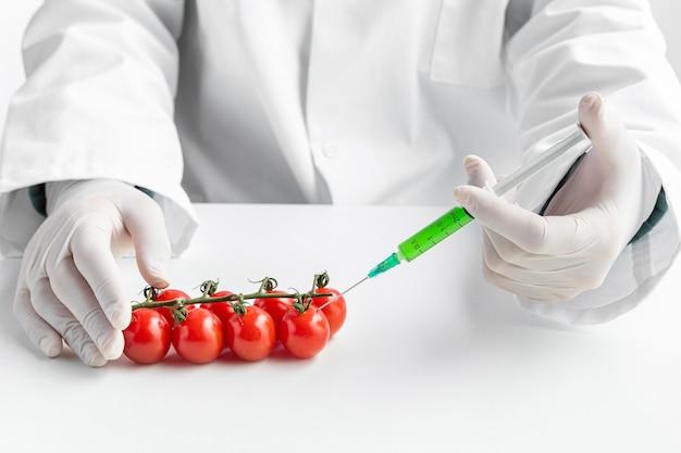 Vista frontal tomates cherry inyectados con productos químicos
