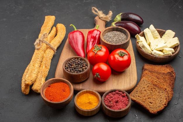 Vista frontal de tomates rojos frescos con pan y diferentes condimentos en el espacio oscuro