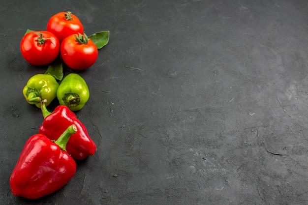 Vista frontal de tomates rojos frescos con pimientos sobre fondo oscuro