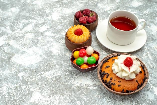 Vista frontal de la torta de chispas de chocolate con una taza de té y caramelos sobre fondo blanco pastel dulce galleta bizcocho de azúcar