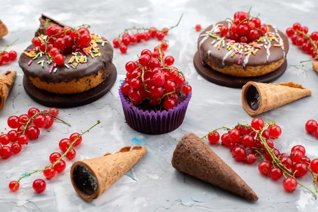 Una vista frontal de tortas de chocolate con rosquillas diseñadas con frutas y cuernos sobre el fondo blanco pastel biscuit donut chocolate