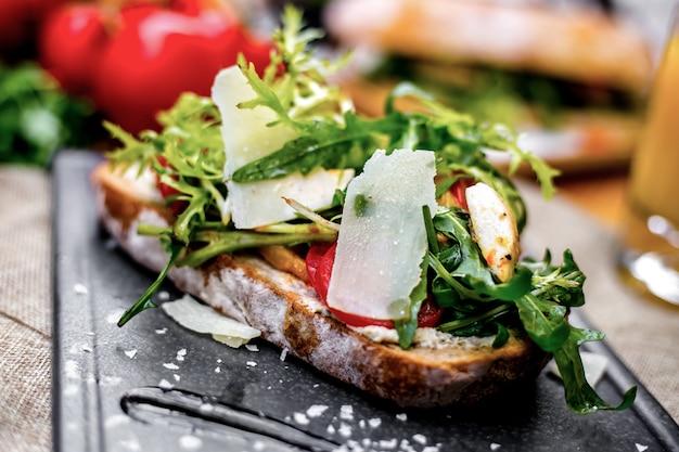 Vista frontal tostadas con verduras rúcula y queso en una bandeja
