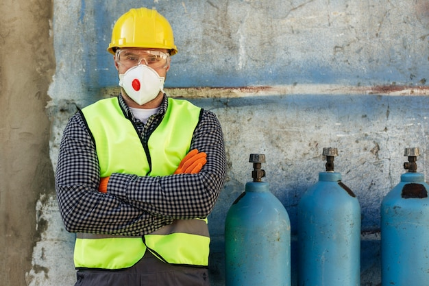 Vista frontal del trabajador con casco y máscara protectora