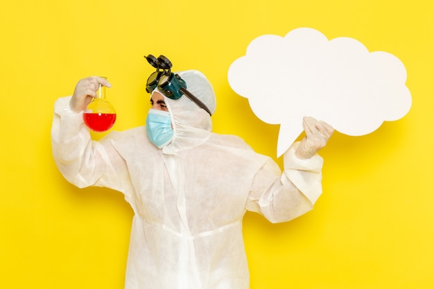 Vista frontal trabajador científico masculino en traje de protección especial con matraz con solución roja gran cartel blanco sobre superficie amarilla