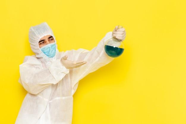 Vista frontal del trabajador científico masculino en traje de protección especial sosteniendo el matraz con solución verde en la pared amarilla