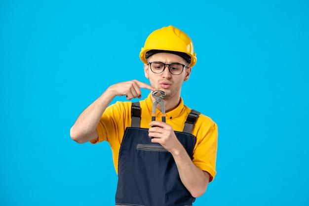 Vista frontal del trabajador masculino en uniforme y casco con pinzas en azul