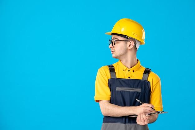 Vista frontal trabajador masculino en uniforme y casco tomando notas sobre azul