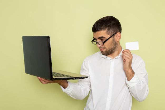 Vista frontal del trabajador de oficina masculino en camisa blanca con computadora portátil y tarjeta en la pared verde claro