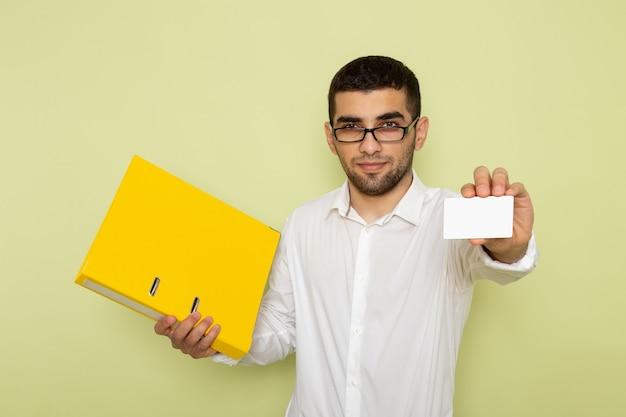Vista frontal del trabajador de oficina masculino en camisa blanca con tarjeta y archivos amarillos en la pared verde