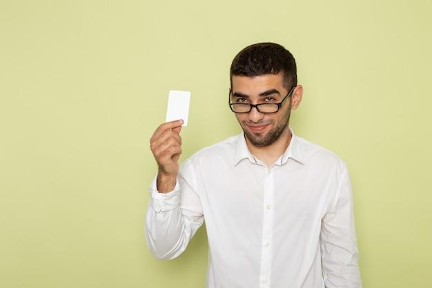 Vista frontal del trabajador de oficina masculino en camisa blanca con tarjeta con sonrisa en la pared verde claro