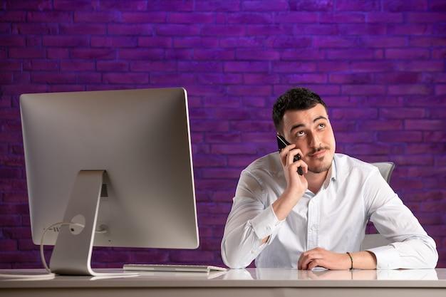 Vista frontal trabajador de oficina masculino sentado detrás de su lugar de trabajo hablando