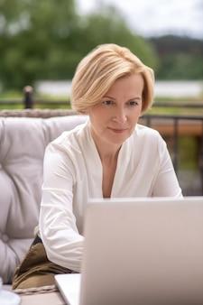 Vista frontal de una trabajadora autónoma caucásica de mediana edad centrada seriamente trabajando en su computadora portátil al aire libre