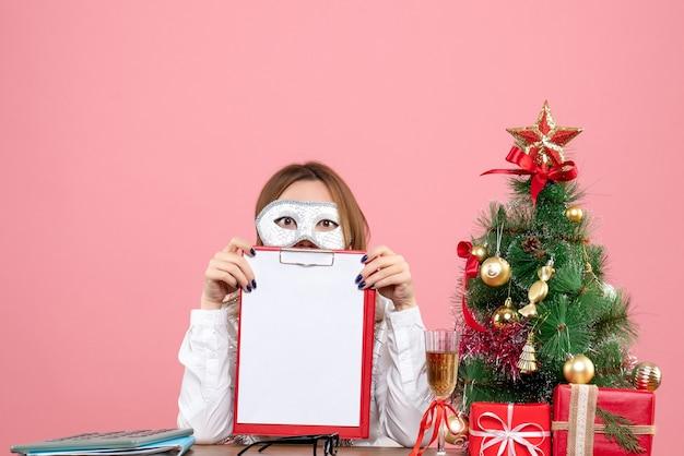 Vista frontal de la trabajadora en la máscara del partido con nota de archivo en rosa