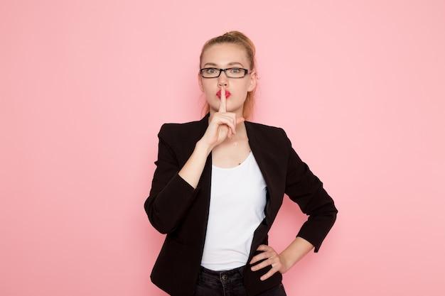 Vista frontal de la trabajadora de oficina en chaqueta negra estricta que muestra el signo de silencio en la pared rosa