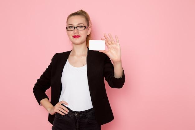 Vista frontal de la trabajadora de oficina en chaqueta negra estricta sonriendo sosteniendo una tarjeta blanca en la pared rosa