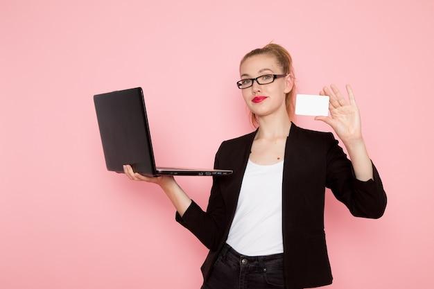 Vista frontal de la trabajadora de oficina en chaqueta negra estricta sosteniendo la tarjeta y usando su computadora portátil en la pared rosa