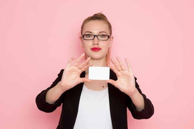 Vista frontal de la trabajadora de oficina en chaqueta negra estricta con tarjeta de plástico blanca sonriendo en la pared de color rosa claro