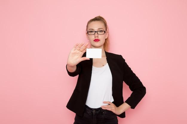 Vista frontal de la trabajadora de oficina en chaqueta negra estricta con tarjeta de plástico en la pared de color rosa claro