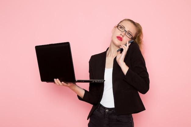 Vista frontal de la trabajadora de oficina en chaqueta negra estricta usando su computadora portátil en la pared rosa