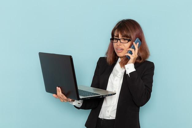 Vista frontal de la trabajadora de oficina hablando por teléfono y sosteniendo la computadora portátil en la superficie azul
