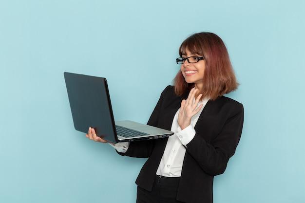 Vista frontal de la trabajadora de oficina en traje estricto sosteniendo el portátil usándolo en la superficie azul