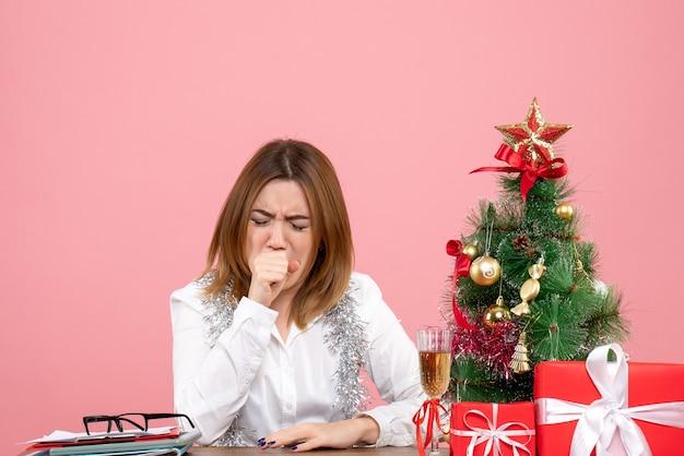 Vista frontal de la trabajadora sentada alrededor de regalos de navidad tosiendo en rosa