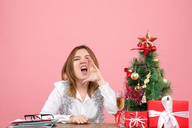 Vista frontal de la trabajadora sentada detrás de su mesa con regalos llamando en voz alta a rosa
