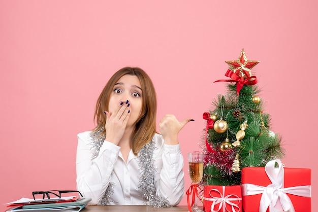 Vista frontal de la trabajadora sentada detrás de su mesa en rosa