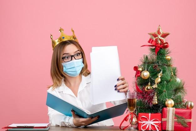 Vista frontal de la trabajadora sentada en una máscara estéril con documentos en rosa