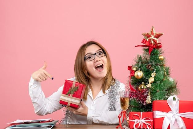 Vista frontal de la trabajadora sentada con regalos de navidad en rosa