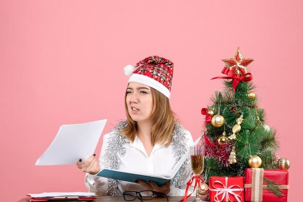 Vista frontal de la trabajadora sosteniendo documentos en rosa