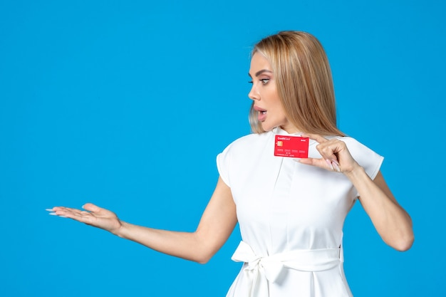 Vista frontal de la trabajadora con tarjeta bancaria roja en la pared azul