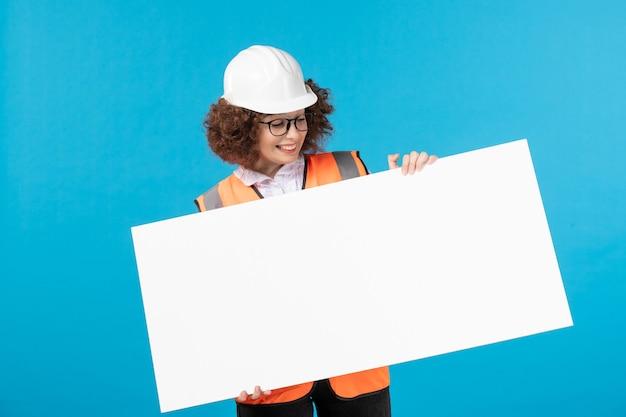Vista frontal de la trabajadora en uniforme en la pared azul