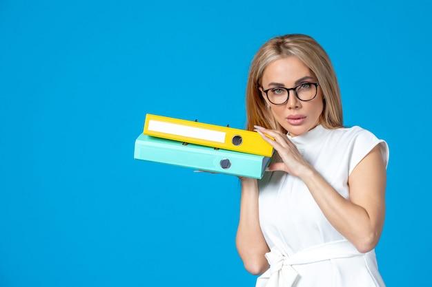 Vista frontal de la trabajadora en vestido blanco sosteniendo una carpeta diferente en la pared azul
