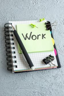 Vista frontal del trabajo nota escrita en la pegatina verde con el bloc de notas y un bolígrafo en la superficie blanca color oficina de trabajo cuaderno escolar colegio de negocios