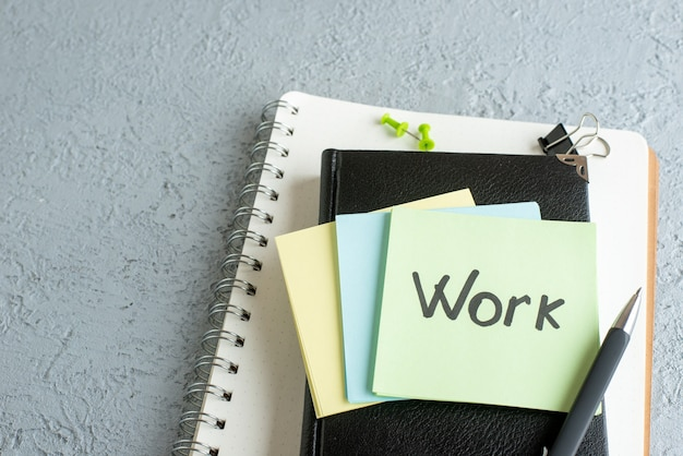 Vista frontal trabajo nota escrita en pegatinas con bloc de notas y lupa sobre superficie blanca trabajo universitario oficina escolar color de cuaderno de negocios