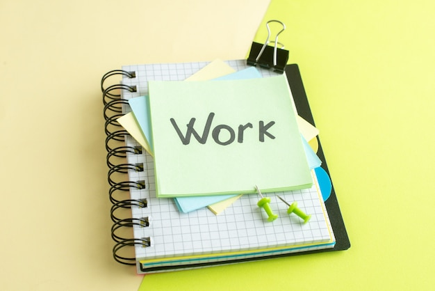 Vista frontal trabajo nota escrita en pegatinas sobre una superficie amarilla oficina de trabajo de la universidad copybook color fotografía de la escuela dinero de negocios salario