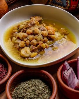 Vista frontal tradicional plato azerbaiyano piti con hierbas y cebollas secas de zumaque