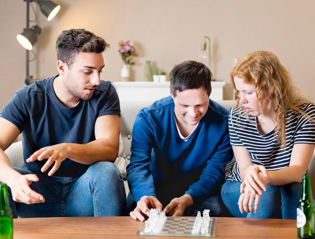 Vista frontal de tres amigos en casa jugando al ajedrez