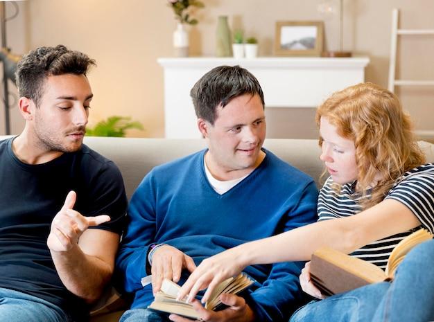Vista frontal de tres amigos leyendo en el sofá en casa