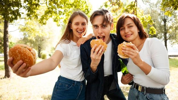 Vista frontal de tres amigos en el parque con cerveza y hamburguesas.