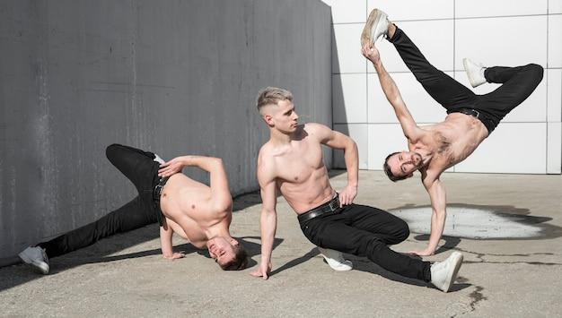 Vista frontal de tres artistas de hip hop sin camisa bailando