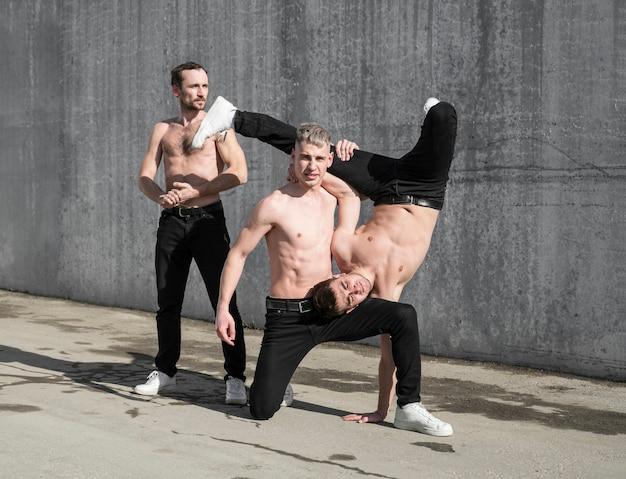 Vista frontal de tres artistas de hip hop sin camisa posando afuera mientras baila