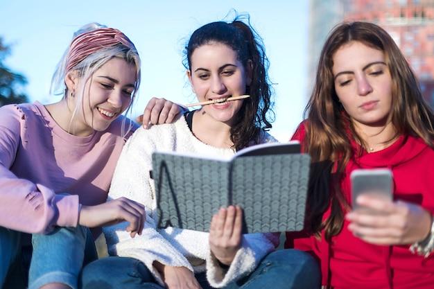 Vista frontal de tres chicas sentadas en el suelo al aire libre.