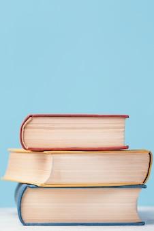 Vista frontal de tres libros apilados de colores con espacio de copia