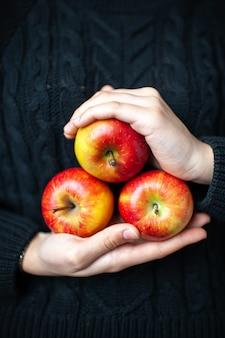 Vista frontal de tres manzanas rojas maduras en manos de mujer
