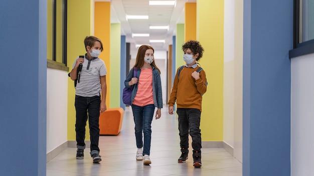 Vista frontal de tres niños en el pasillo de la escuela con máscaras médicas