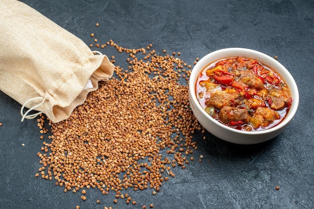 Vista frontal de trigo sarraceno crudo con sopa de carne en el espacio gris